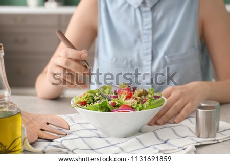 Woman eating tasty quinoa salad at table #1131691859
