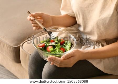 Woman eating tasty salad at home, closeup #1505368088