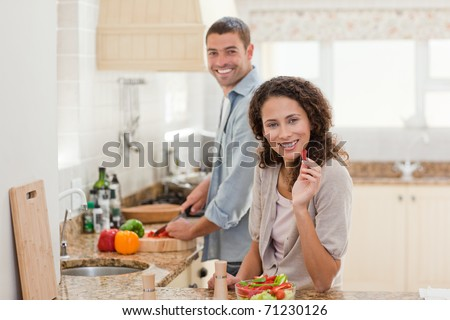 Woman eating while her husband is cooking at home
