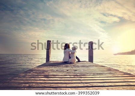 woman embracing sweetly his dog while looking the view #399352039