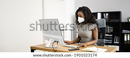 Woman Employee In Office Wearing FFP2 Face Mask Working On Computer ストックフォト ©