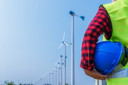Woman engineer in uniform and holding blue safety helmet with standing and checking wind turbine power in construction site renewable energy. Clean energy and environment concept.