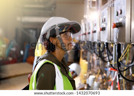 Woman Engineers electrical control with safety helmet and safety glasses for industrial estate or power plant background. Industry concept. #1432070693