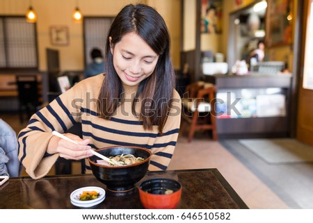 Woman enjoy udon in Japanese restaurant #646510582