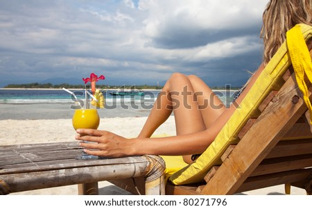 Woman enjoying a cocktail on a tropical beach