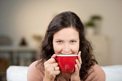 Woman enjoying a large cup of freshly brewed hot tea as she relaxes on a sofa in the living room