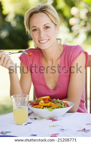 Woman Enjoying A Salad In A Garden