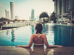Woman enjoying a swim in a luxurious high rise pool.