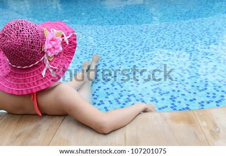 woman enjoying a swimming pool in a large sunhat