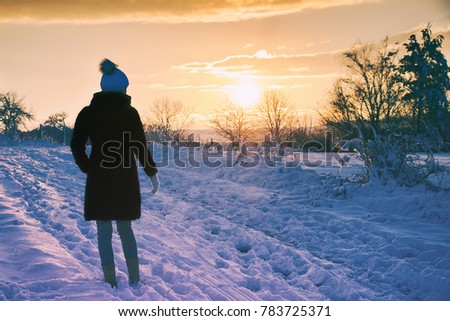 Stock Photo woman enjoying a walk in winter landscape during sunset, beautiful snow-covered countryside. girl wearing coat and winter hat.