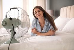 Woman enjoying air flow from fan on bed in room. Summer heat