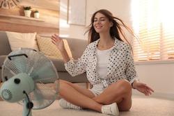 Woman enjoying air flow from fan on floor in living room. Summer heat