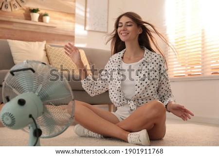 Woman enjoying air flow from fan on floor in living room. Summer heat Foto d'archivio ©