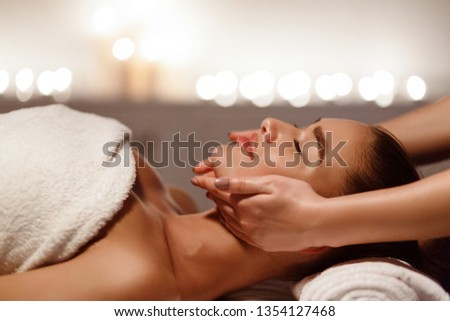 Woman enjoying anti aging facial massage at wellness center, side view