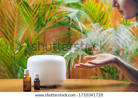Woman Enjoying Aroma Therapy Steam Scent from Home Essential Oil Diffuser or Air Humidifier. Ultrasonic technology, increasing air humidity indoors for more comfortable living conditions Stock foto ©