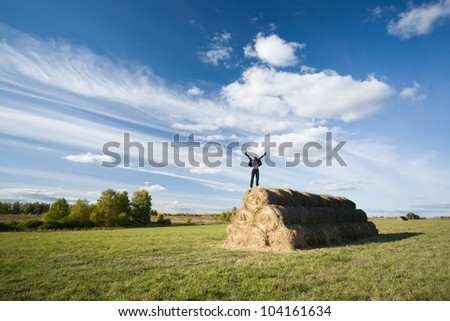 Woman enjoying beautiful sunny evening at haystack at field - stock photo