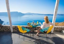 Woman enjoying breakfast with beautiful view from terrace