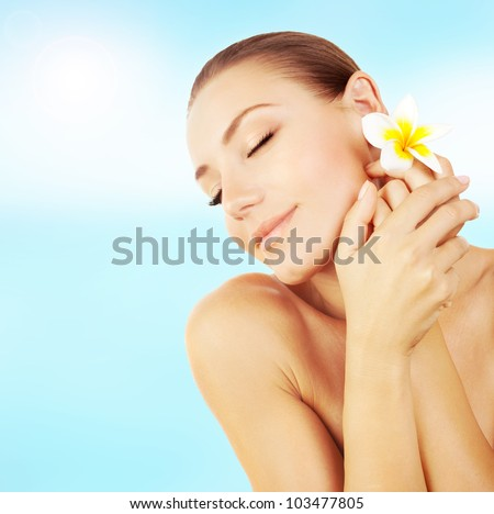 Woman enjoying day spa resort; beautiful peaceful relaxed female on the beach; applying cream; hand massage; face with frangipani flower; healthy model girl outdoor; wellness and body care concept