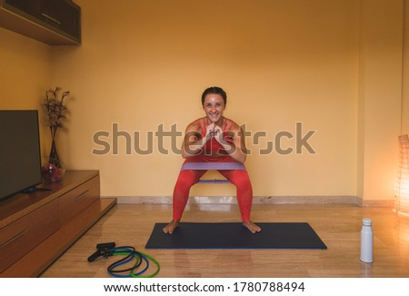 Woman enjoying exercising in the living room with some tapes. Beautiful caucasian woman working at home for the coronavirus. Brunette woman in squatting position working buttocks.