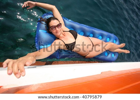 Woman enjoying her summer on a lilo on the sea