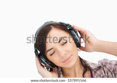Woman enjoying music with headphone against white background