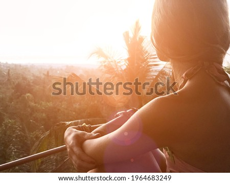 Woman enjoying panoramic landscape view on a rainforest in Bali, Indonesia.