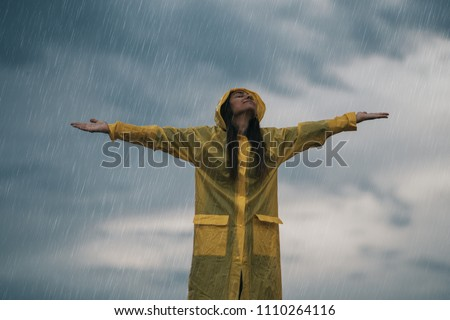 Woman enjoying rainy grey autumn day outdoors. soft daylight.