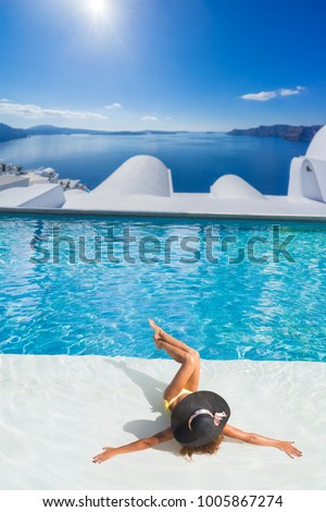 Woman enjoying relaxation in pool and looking at the view in Santorini Greece - Shutterstock ID 1005867274