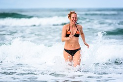 Woman enjoying sea and waves of Atlantic ocean. Mature, mid aged, young attractive woman in bathing suit bikini is running in the ocean sea, playing and sprinkling the water. Atlantic ocean - Portugal