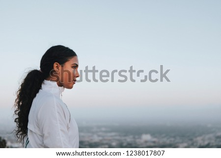 Woman enjoying the city view from a hill #1238017807