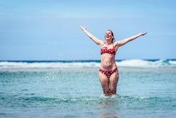 Woman enjoying the sea and waves of Atlantic ocean. Mature, mid aged, young attractive woman in bathing suit is walking in the ocean sea playing and sprinkling the water. Atlantic ocean Galicia, Spain
