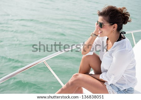 Woman enjoying the summer vacations sailing in a boat