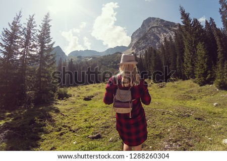 Woman enjoying the view at the beautiful alpine lake Seebensee near Ehrwald, Tyrol, Austria. Rocky mountains under blue sky in the background #1288260304