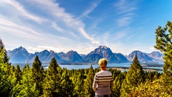 Woman enjoying the view of Jackson Lake and the tall mountain peaks of the Teton Range viewed from Signal Mountain in Grand Teton National Park in Wyoming, United States