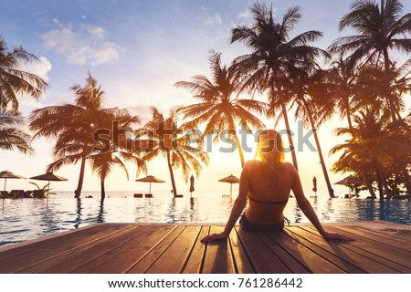 Woman enjoying vacation holidays at luxurious beachfront hotel resort with swimming pool and tropical lansdcape near the beach