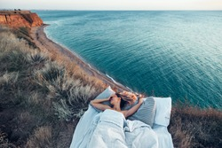 Woman enjoying view on beach landscape while relaxing in bed on mountain in sunset on the edge of Earth. Calm and quiet wanderlust concept moment when person feels happiness and freedom.