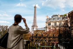Woman enjoying view on the Eiffel tower in Paris. Image focused on the background
