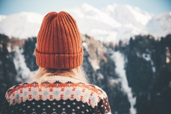 Woman enjoying winter mountains wearing cozy sweater and hat Travel Lifestyle adventure concept vacations into the wild