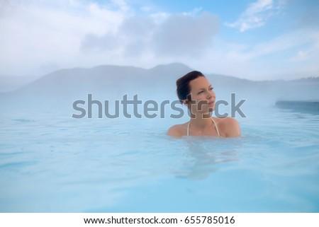 Woman enjoys spa in geothermal hot spring