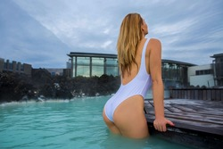 Woman enjoys spa in hot spring Blue Lagoon in Iceland. Dramatic sky. Beautiful colors