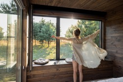 Woman enjoys sunrise in a country house or hotel staying with open hands near panoramic windows with pine forest view. Good morning and recreation on nature concept. Back view