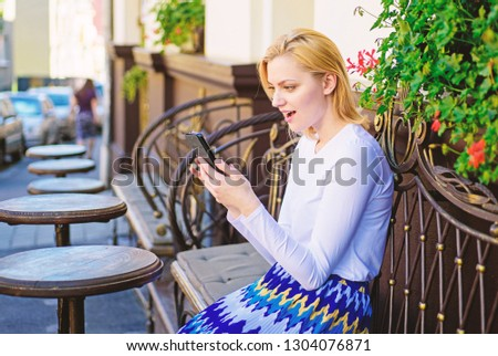Woman enthusiastic face with smartphone create appointment in social network and wait friends cafe terrace. Girl wait meeting with friends. Arrange appointment in social network. Make appointment.