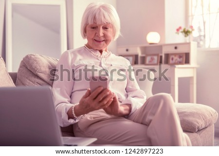 Woman enthusiastically monitoring. Beautiful elder woman enthusiastically monitoring her mobile phone having a laptop nearby