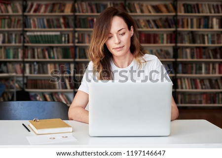 Woman entrepreneur working on laptop at co-working office or library, looks smart, bookshelves. Knowledge and self-development.