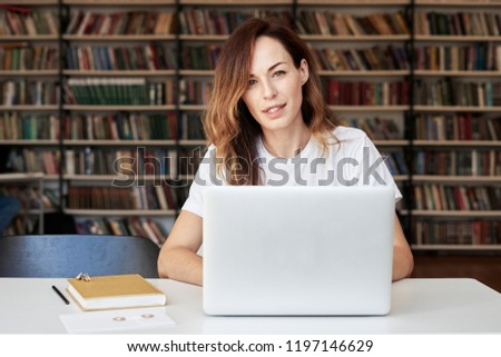 Woman entrepreneur working on laptop at co-working office or library, looks to camera, smart, bookshelves. Knowledge and self-development.