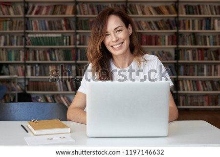 Woman entrepreneur working on laptop at co-working office or library, looks to camera, smiling, bookshelves. Knowledge and self-development.