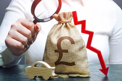 Woman examines a british pounds sterling money bag with a red down arrow and automobile. Car insurance, taxes, maintenance. Fuel excise taxes. Electric vehicle support subsidies.