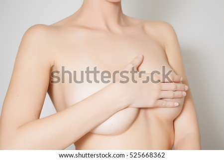 Woman examines her breast