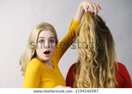 Woman excited looking on her female friend long ombre color hair. Hairdo colors, haircare and hairstyling.