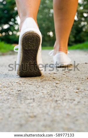 Woman exercise walking outdoors, shoes closeup. Runner or jogger training outside in summer nature, health and fitness